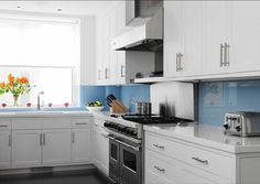 a much better brighter blue [katie+ridder+eat+in+kitchen+blue+glass+large+wall+tile+backsplash+quartz+stone+white+countertips+cabinets+brushed+metal+pulls+stainless+steel+appliances.jpg]
