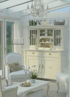 White chairs, Cupboard, Baskets, Chandelier, white coffee table