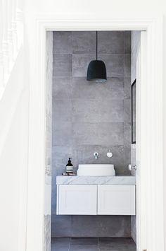 **Bathroom** Mottled grey tiles from [Teranova Tiles] echo the honed carrara marble vanity top. A Mud australia pendant light and Omvivo 'Latis' basin cut modern and clean silhouettes. Grey Bathroom Tiles, Grey Bathrooms, Laundry In Bathroom, Bathroom Layout, Bathroom Fixtures, Beautiful Bathrooms, Modern Bathroom, Small Bathroom, Bathroom Ideas