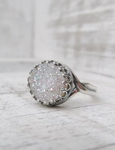 This beautiful ring features a fabulous white druzy quartz with brilliant iridescence color. The stone measures 10mm with a Grade A fine