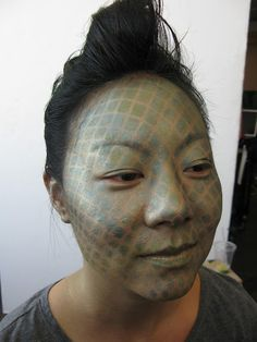 Scaley skin achieved by placing a fishnet stocking over the face and dabbing makeup over it. - Genius!