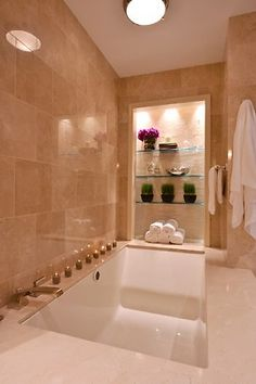 Sophisticated and luxurious bathtub with built in shelving. via porch.com