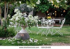 White table and chairs in beautiful garden.