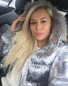 Beautiful princess in soft shiny downjacket with fur hood