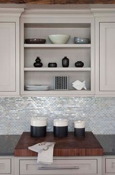 watery glass backsplash tiles and counters made of recycled glass reflect the light, add polish and contrast with the rough-hewn post and beam construction. A walnut cutting board relates back to the thick beams and barn wood.- contemporary kitchen by Arturo Palombo Architecture
