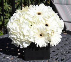 Pure white hydrangeas accented with white gerberas with black centers in a black square ceramic vase. Simple yet classy.  $40.00