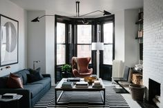 A black and white striped rug covers the floor of a masculine living room.