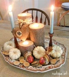 Fall / Thanksgiving centerpiece - candle holders = tree trunk sections with drilled recess for tea lights; surround with small pumpkins, tree branch slices or nuts, wooden candlesticks, metal heart & raffia on pretty platter