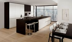 Cocina sin tiradores laca alto brillo blanca, acentuada en laca alto brillo negra. Encimeras de granito negro.  Handlesless kitchen in high gloss lacquer white accented with high gloss lacquer black.  Black granite worktops.