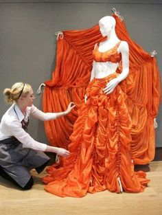 A Christie's staffer adjusts a Norma Kamali parachute skirt and bustier on display at the auction house in London, 2008. Credit: Sang Tan / Associated Press
