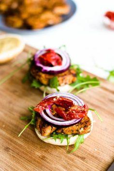 Hamburger mit Hühnerfleisch, Rucola, getrockneten Tomaten und roten Zwiebeln