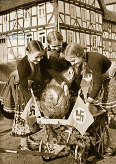 Farm bread being sent to the poor people in the city, from 'Germany: The Olympic Year', pub. by Volk und Reich Verlag Berlin, 1936 (sepia photo)