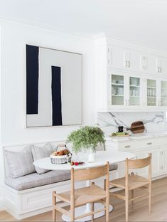White cabinets, grey cushions, white oval tulip base table, monochrome art, wooden chairs