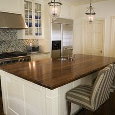 Love the white cabinets with the black walnut topped island.