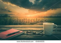 Pen, opened notebook, glasses, and coffee cup on outdoor wood table in morning time on weekend with landscape view in blurry background. Weekend morning lifestyle concept with vintage filter effect