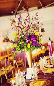 """For a Moroccan themed wedding - deep purple and yellow flowers and lots of metallic gold. Love the votive candle """"lanterns"""" hanging in the branches"""