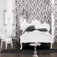 Black and white bedroom. Damask wallpaper. Chandelier. White elaborate carved bed. Modern white chair. Silver side tables.