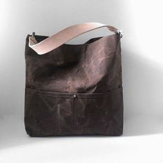 A casual bucket bag, in Earth-y Dark Brown Waxed Canvas that is durable, lightweight and a breeze to carry. This rugged, natural canvas bag ages beautifully and looks better with a little wear and tear; becoming softer and more creased with use; giving it that sought after well-worn, lived in look. Our bucket tote has an easy-carry-shape and includes 5 slip pockets (2 outside and 3 inside) as well as a large interior zippered pocket. A double-wide, natural leather strap and nickel plated…
