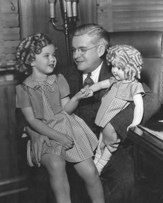 Shirley Temple introduced to herself in doll-form, mid 1930s.  Her face looks very peculiar in this photograph.