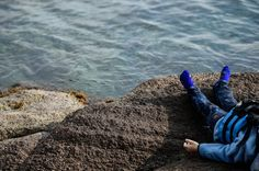 The body of a child lies by the beach in Canakkale's Bademli district on January 30, 2016 after at least 33 migrants drowned when their boat sank in the Aegean Sea while trying to cross from Turkey to Greece, Turkey's state-run Anatolia news agency reported.