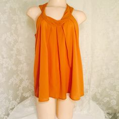 Orange sleeveless blouse with gold-colored buttons Orange sleeveless blouse with gold-colored buttons. 100% polyester Tops