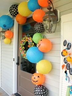 Delight Your Trick-or-Treaters with These 10 Easy D.I.Y.s -  Paper lanterns and pumpkin buckets - For an instantaneous and easy porch design, grab a few adhesive command hooks to hang dollar-store pumpkin baskets and colorful paper lanterns around your front door.