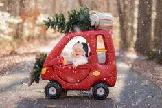 Baby in auto met kerstboom boven op