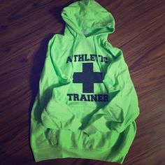 Athletic Trainer Neon green athletic trainer sweatshirt. Perfect for visibility and I'm sure your athletic trainer friend would greatly appreciate it. It's 50% cotton and 50% polyester. Has been washed and the black writing is a little faded but other than that it's wonderful! It is a size xl and I'm a small but I do love layering when it's cold out! Sweaters