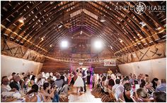 A wide shot of the groom kissing his bride at the end of their first dance as their guests look on at the D-Barn also known as Dickens Barn in Longmont, Colorado. - April O'Hare Photography http://www.apriloharephotography.com #ColoradoWedding #OldMillPark #Longmont #Colorado #LongmontWedding #ColoradoRusticWedding #HistoricSite #RedBarn #DBarn #LongmontBarnWedding #DickensBarn #StringLights