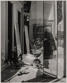 This 1958 photograph is one of #ImogenCunningham's best-known self-portraits. She appears as a diminutive figure in a dark cape reflected in the facets of an abandoned shop window on Geary Street in San Francisco.