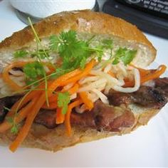 To assemble the bahn mi sandwich, fill the cavity of the bottom half of the bread with either broiled chicken or beef, cucumber slices, pickled carrot, onion, and radish, cilantro leaves, and jalapeno pepper. Squeeze a wedge of lime over the filling, and top with the other half of the baguette.