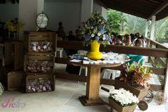 Decoração com vaso de hortênsias, caixotes e carrinho de mão.