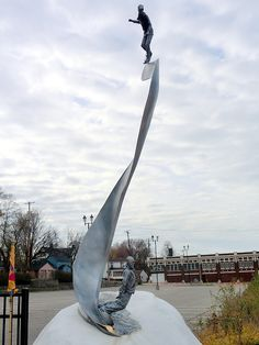 Grandaddy of Snowboarding~an 18' tall sinuous ribbon of shiny metal depicts a young girl on a strange contraption lunging down a flowing river, while another figure decked out in winter gear gazes up at her approach. This svelte & fluid bronze sculpture hints at an event that revolutionized winter sports & put Muskegon, MI, on the international map.