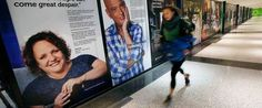 A passenger rushes past an art exhibit at Logan International Airport in Boston, Thursday, Dec. 8, 2016. The exhibit consists of larger-than-life posters of nearly three dozen people _ some ordinary, some famous _ who have struggled with mental illness.  Michael Dwyer  - AP Photo