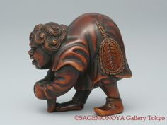Dutchman shaking a stone from his right shoes. Wood Netsuke. Signed TSUJI. 18th C. 靴を履く和蘭陀人。木刻 根付。 銘 辻。