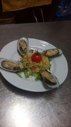 Cous cous di pesce decorato con cozze mezzo guscio e pomodoro fritto