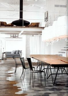 This hexagonal tile floor by designer Paola Navone acts as a dining area rug, fading to worn wooden planks at the edges.