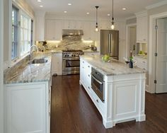 This gorgeous transitional kitchen is carefully designed to look stylish yet timeless. A wall of windows and fresh white cabinets create a bright, cheery atmosphere, while stunning granite countertops lend depth and movement to the space. Rich hardwood floors provide a dose of warmth, and stainless steel appliances ensure a polished finish.