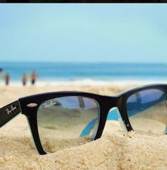 Clear glasses in the sand with the beach behind- neat photo idea