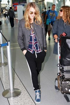 Cara Delevingne wears a plaid shirt, bomber jacket, athletic pants, high-top sneakers, and round sunglasses