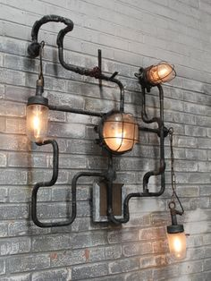 Bespoke industrial wall light made with conduit piping in a blackened galvanised finish. An assortment of vintage bulkheads, pendants and reclaimed gas taps are hung from the frame. Conduit Lighting, Garage Lighting, Park Lighting, Home Lighting, Industrial Wall Lights, Industrial Pipe Shelves, Vintage Industrial Furniture, Steampunk Lamp, Metal Wall Decor