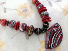 Collier ethnique style péruvien multicolore tons rouges dominants, grand pendentif forme éventail : Collier par agape
