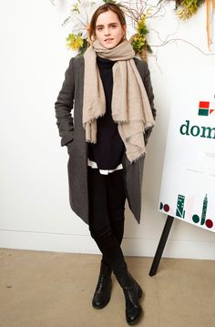 Emma Watson in a black top, pants, tan scarf and gray coat