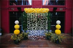 Yellow ombre floral curtain for the altar with carnations and mums and flower topiaries of daisies. #ombrewedding