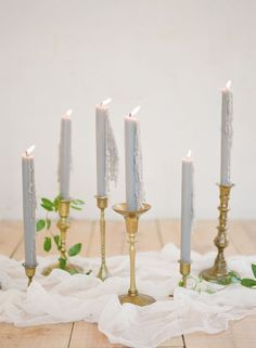 Wedding table inspiration: Use dusty blue candles in brass candle holders to create an elegant, romantic effect. Photography : Feather And Stone