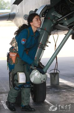 One of the ten first Chinese female JH-7A pilots doing a preflight check of her fighter-bomber Xian JH-7A, at an undisclosed air base in Shandong Province, China, on July 2, 2015.