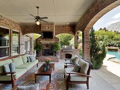 Luxury Patio Ideas - covered patio with brick fireplace and brick arches and columns open to a swimming pool on the right -LifetimeLuxury016