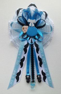 mustache theme mommy baby shower corsage with baby in blue swaddle