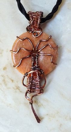 Simple and beautiful. A rustic salmon colored gemstone donut is wrapped in heavy copper wire and antiqued by hand. The bail and base are hand woven. This solid piece has an art deco, artsy feel.