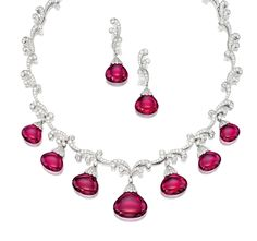 RUBELLITE AND DIAMOND NECKLACE & PAIR OF MATCHING PENDENT EAR CLIPS, TIFFANY & CO.  Composed of seven graduated rubellite drops together weighing approximately 90.00 carats, supported by scrolls of brilliant-cut diamonds, length approximately 380mm; & pair of matching pendent ear clips, each suspending a rubellite drop altogether weighing approximately 20.00 carats, to a similarly-set surmount, clip fittings; mounted in platinum, signed and numbered.